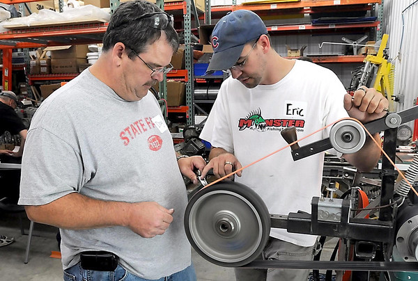 Eric Poris helps Doug Sutherland work on a blade during Saturday's Hammer In.