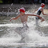 A competitor in the Intermediate Division splashes into first leg of the Ironkids Triathlon as another heads for the riding portion of the race.