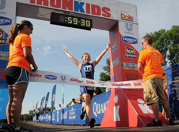 John Cross<br /> Ironkids competitor Hannah Higgins of Byron, Minn., raises her arms and sports a smile as she crosses the finish line.
