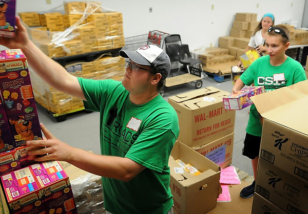 John Cross<br /> From left, Levi Bentdahl, Sam Csizmadia and Madison Bentdahl stack boxes of cereal at the ECHO food shelf on Monday. Nearly 40 youth will be doing volunteer work at various Mankato sites this week through CSI (Christ's Servants Involved ) Mankato.
