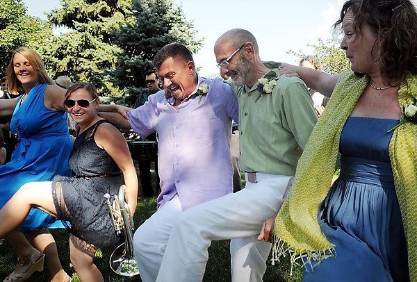 Rob Thomas (left) and Joe Strong join guests in a line dance following their wedding ceremony at the Nicollet County Courthouse in St. Peter on Thursday.