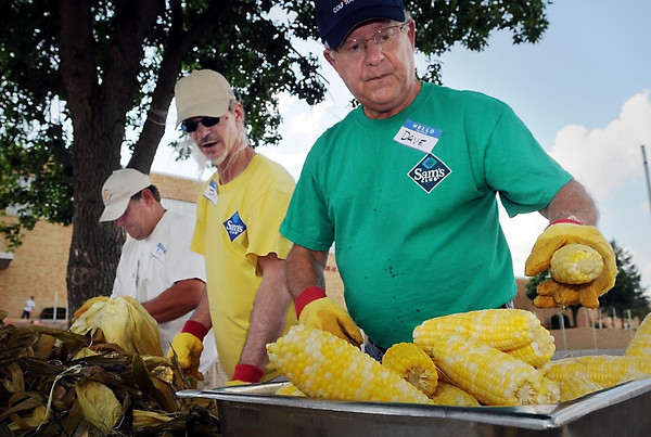From left, Roger Kruger, Jack Fitzpatrick and Dave Lang shuck steaming ears of sweet corn to be served to hungry diners Monday at the 55th annual Y's Club Corn Roast at West High School. Money raised during the event goes to support youth programs at the YMCA.