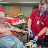 Rob Knapp (right) scans vials of blood drawn from Dave Hageman (left) during a blood drive held at the Mankato Public Safety Center on Friday. Marah Bengston, who organized the blood drive, said the turnout was good with 33 appointments scheduled and two walk ins. Photo by Jackson Forderer