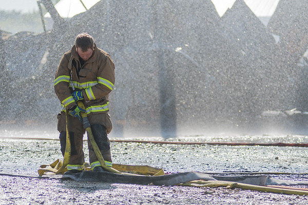 Nate Boomgarden of the Madelia Fire Department picks up a hose as the city's street maintenance building was getting sprayed down by another firefighter on Thursday. A street sweeper and a dump truck were lost in the blaze.<br /> Photo by Jackson Forderer