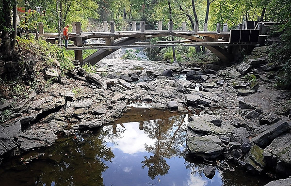 John Cross<br /> There is little water flowing beneath the bridge at Minneopa State Park after prolonged conditions over the summer have reduced Minneopa Creek a mere trickle. The 90-year-old bridge is in the process of being dismantled to make room for a new one.