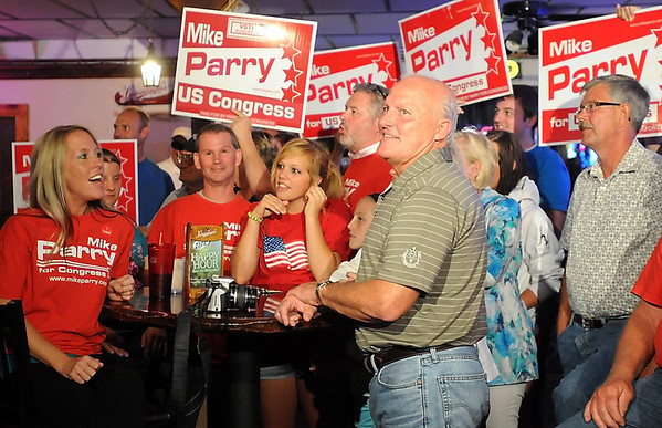 Supporters hold up signs as state Sen. Mike Parry watches Republican primary election results during a gathering at Katie O'Leary's in Waseca. Parry and former state representative Allen Quist are vying to be the Republican challenger for Democratic U.S. Sen. Tim Walz's seat.