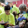 Lynn Guhlky of Lake Crystal, Minn., is examined by volunteer dentist Dr. Richard Wiberg as dental assistant Kerrie Schutt takes notes, Friday, at a Mission of Mercy dental Clinic at the Verizon Wireless Center.