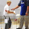 Judge Mark Peterson talks with 9-year-old Elijah Drummer of Nicollet about his market chicken during the Tri-County Fair Wednesday in Mankato.