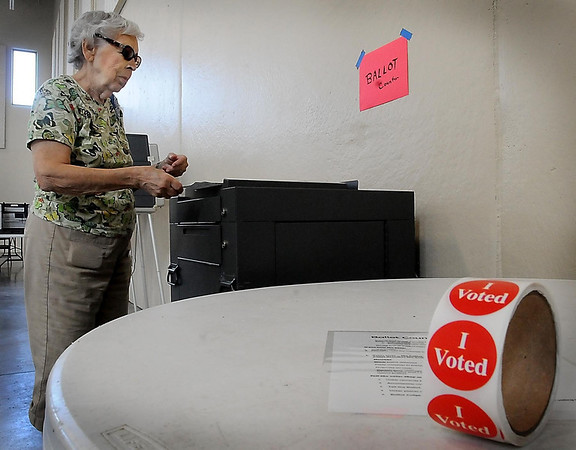 John Cross<br /> Elaine Dutcher places her primary election ballot in the ballot counter Tuesday at the National Guard Armory, a new location this year for Precinct 15 voters.