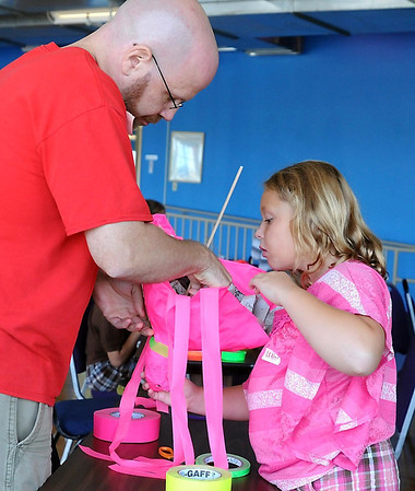 Dave DeGennero helps Leah Klint, 8, put the finishing touches on her pink squid for the Monkey Mind Pirates puppet show program Wednesday at the YMCA.