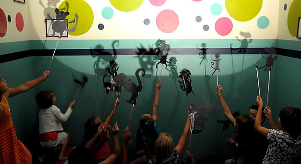Children practice making shadows with their monkey puppets during a rehearsal for the Monkey Mind Pirates puppet show program Wednesday at the YMCA. The show is steeped in themes of finding calm and reeling in a racing mind.