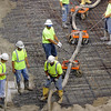 Pat Christman <br /> Workers use dollys to support a hose full of concrete as they pour the new floor for the Verizon Wireless  Center Tuesday.