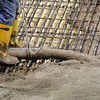Pat Christman <br /> Concrete flows over support bars and refrigerant pipes during Tuesday's pour.