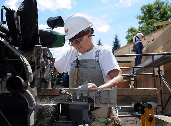 John Cross<br /> Habitat Care A Van member Dori Peters of Sun City, Ariz., makes cuts with a power miter saw at a home construction site on Rogers Street  near Sibley Park.