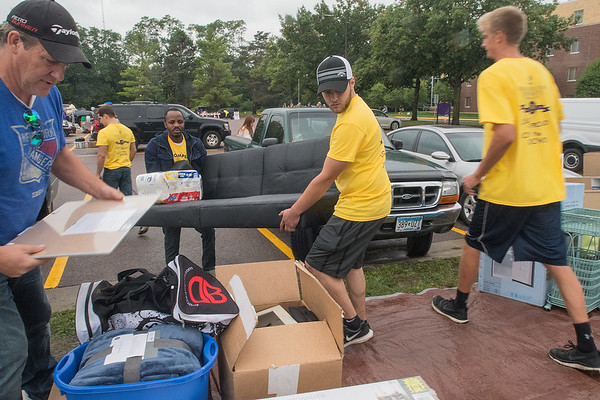 Minnesota State University juniors Brandon Carlson (second from right) and Ricky Mayega carry a futon for a fellow student to put on a tarp during a rainy move in day on Thursday. Classes begin on Monday for MSU students. Photo by Jackson Forderer