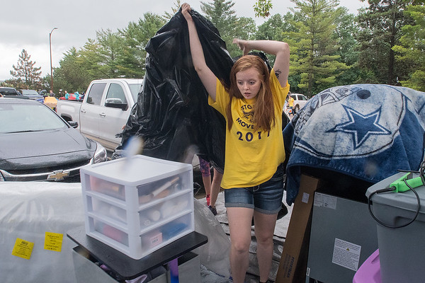 "Freshman Corynne McNiesh pulls a tarp to a dry spot during a rainy move in day at Minnesota State University on Thursday. ""We got to move in early yesterday,"" said McNiesh, as one of the benefits of volunteering to help fellow students move in. Photo by Jackson Forderer"
