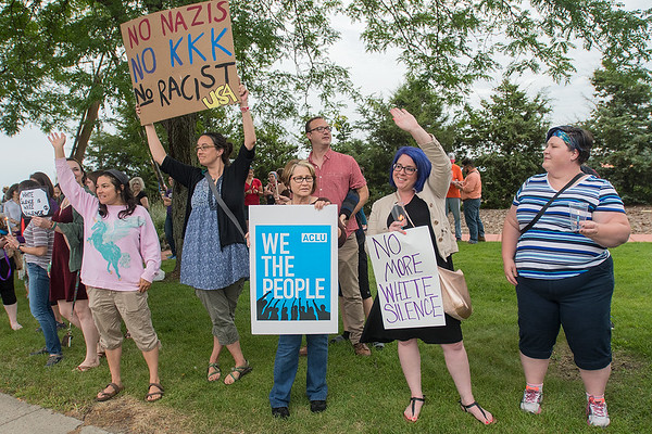 From left, Drea Brown, Melissa Martensen, Julie Warner and Lisa Finch hold protest signs and wave at traffic during a vigil held for the violence in Charlottesville at Reconciliation Park on Tuesday. Photo by Jackson Forderer