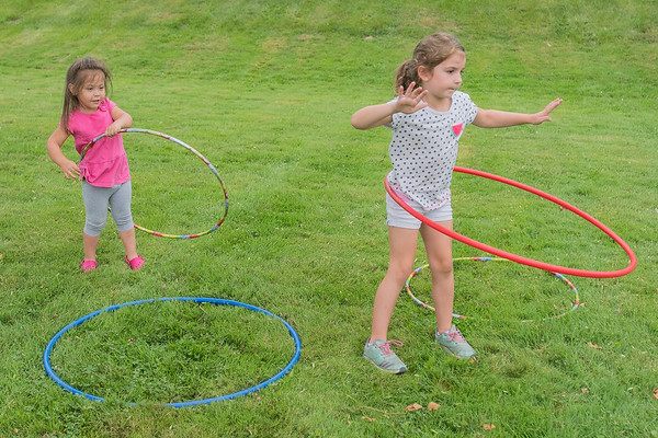 Jema Valle, 3, watches Madison Wersas, 6, hula hoop and follows her lead at the annual YMCA Corn Roast held outside of Mankato West on Monday. Photo by Jackson Forderer