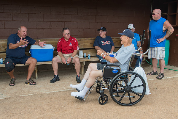 """Tink Larson (right) talks with his friends in the dugout during the reopening of Tink Larson Field in Waseca. """"When I saw it go up in smoke, that was devastation,"""" Larson said of the grandstands that were destroyed by fire, """"today is more like exhilaration."""" Photo by Jackson Forderer"""
