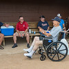 "Tink Larson (right) talks with his friends in the dugout during the reopening of Tink Larson Field in Waseca. ""When I saw it go up in smoke, that was devastation,"" Larson said of the grandstands that were destroyed by fire, ""today is more like exhilaration."" Photo by Jackson Forderer"
