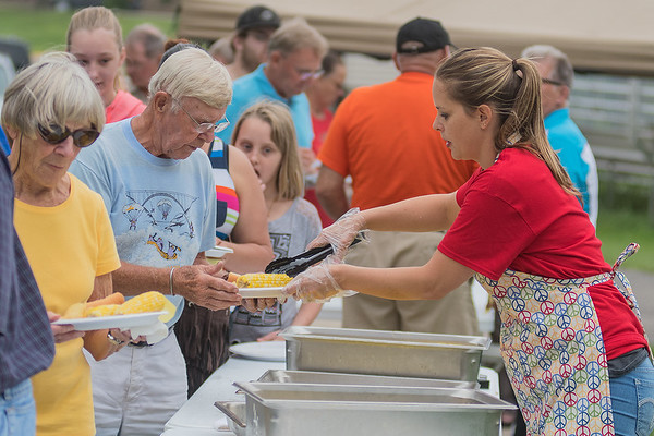 Tami Anderson (right) serves up ears of corn at the annual YMCA Corn Roast held at Mankato West. Photo by Jackson Forderer