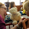 Tiffany Garrioch, a nursing student at Rasmussen College,  positions a stethescope so that Kaylee Voss can listen to her own heart at a Teddy Bear Clinic during children's story hour at the Blue Earth County Library on Tuesday. Photo by John Cross