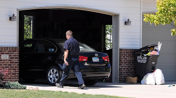 Eagle Lake Police Chief Phil Wills walks in to Minnesota State head football coach Todd Hoffner's home while assisting in an investigation of the coach Tuesday.