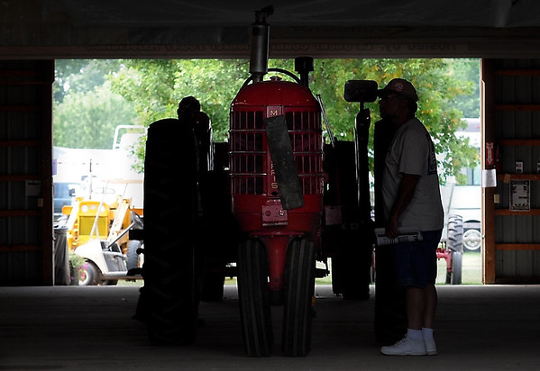 A man looks at a Massey-Harris tractor in a barn at the Pioneer Power Show.
