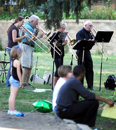 A brass band plays as people chat during a Night to Unite gathering in Washington Park.