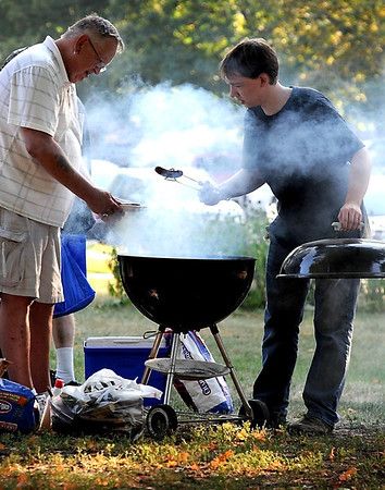 Doug Riebesell (left) and Xach Dinsmore tend to the grill during a Night to Unite gathering Tuesday in Washington Park.