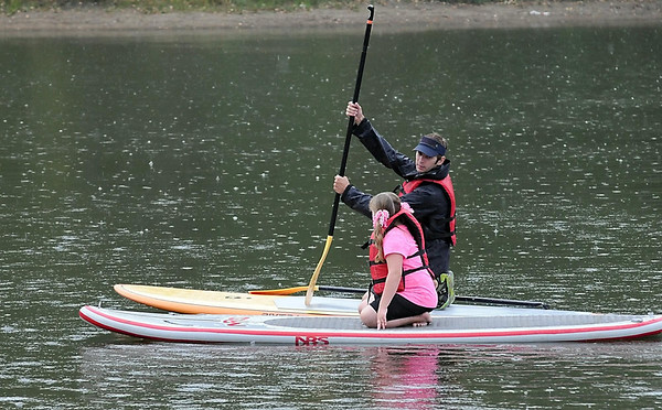 Katelyn Parker, 8, gets some tips from Bent River Outfitters' Dain Fischer on how to paddle a stand up paddleboard during Wellness in the Park Saturday at Hiniker Pond.