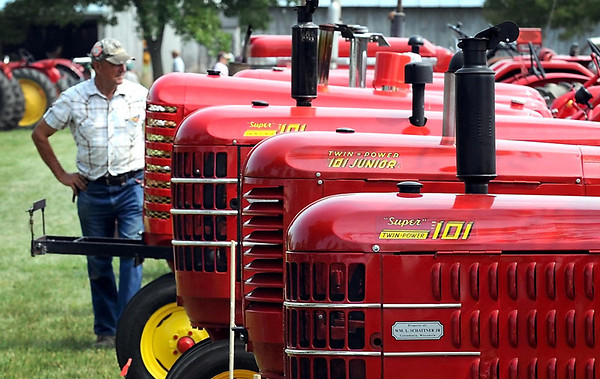 A line of Massey-Harris tractors, the featured tractor at this year's Pioneer Power Show, draws the attention of a visitor to the show's grounds near Le Sueur.