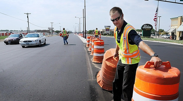 John Cross<br /> Landon Bode and other members of the Mankato City Engineering Department remove traffic barriers Tuesday along Madison Avenue. As of yesterday afternoon, all lanes of traffic on the busy street were re-opened with only lane painting yet to be done. That is expected to be completed today, officially finishing the summer-long project.