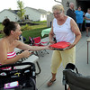 Pat Christman <br /> Host Debbie Mason takes a dessert from a neighbor during her neighborhood's Night to Unite party Tuesday.