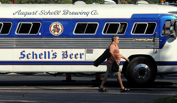 Pat Christman <br /> A man walks past the Schell's tour bus enroute to Jackson Park during the last Alive After 5 of the year Thursday afternoon.