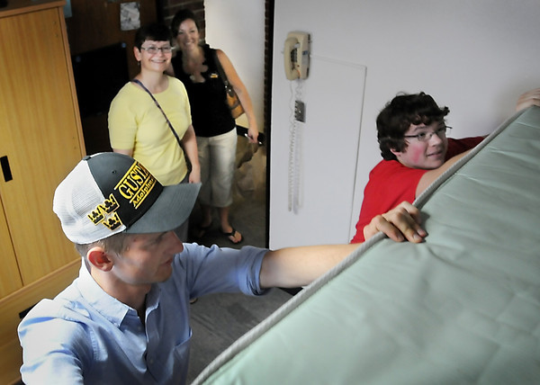 John Cross<br /> Gustavus freshmen roommates William R. Jones (left) and Aaron James Olson arrange their dorm room while their mothers, Beth Jones (left rear) and Susan Olson, both GAC alums, look on during Move-In Day on Friday.