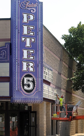 Pat Christman <br /> A worker takes down letters off the marquee of the St. Peter 5 theater Thursday to prepare for the building's demolition. Last week, Nicollet county approved a contract worth $47,600 to demolish the theater ahead of constructing a new building next to the Government Center to consolidate county operations in one block.