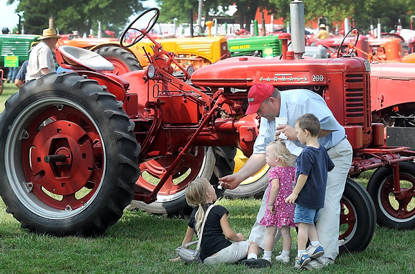 Pat Christman <br /> Joel Enter shares his ice cream with his children, from left, Mary, Esther and Benjamin near a tractor at the Pioneer Power Show Saturday near Le Sueur.