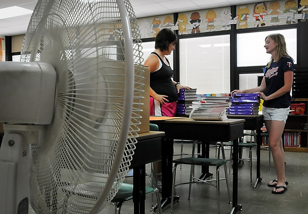 John Cross<br /> A fan offers just a bit of relief from Monday's heat and humidity for Roosevelt fifth grade teachers Sheila Busch (left) and Kris Moore as they prepped for classes that will begin for elementary students in the Mankato Area School District  on Sept. 5. Like many area elementary schools, Roosevelt has no air conditioning.