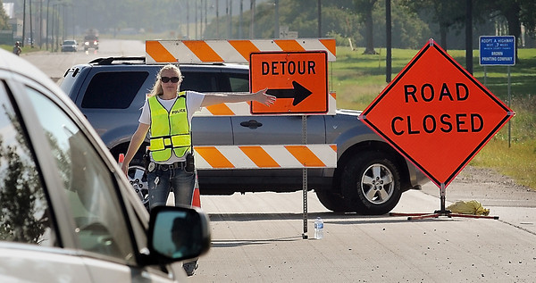John Cross<br /> A Waseca police officer directs traffic away from the Brown Printing plant in Waseca after a chemical spill was reported there.