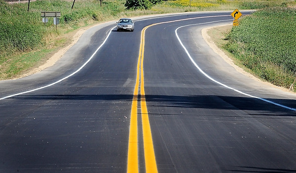 John Cross<br /> A  motorist rolls down a fresh ribbon of asphalt on Blue Earth County Road 17 (Parkway Avenue) into Eagle Lake on Thursday.  A section of the road from Highway 14 east of town to the Eagle Lake City Hall was opened to traffic as other sections of the road west if tiwb were closed down for reconstruction.