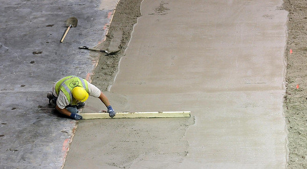 Pat Christman <br /> A worker uses a board to smooth fresh concrete at the edge of the Verizon Wireless Center's new ice arena floor Tuesday morning.