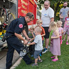 Mankato firefighter Keith Klinder shows children how heavy his rescue equipment is at Night to Unite event outside of Bethlehem Lutheran Church on Tuesday. Photo by Jackson Forderer