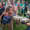 Dajah Williams (second from left), 9, and Madison Ely, 10, blow out a candle on the YMCA's 50th anniversary cake celebrating its brother/sister program on Thursday at Tourtellotte Park. Photo by Jackson Forderer