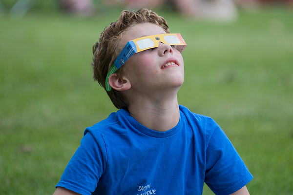 Samuel Shabrack watches the start of the solar eclipse outside of Taylor Library in North Mankato. Local viewers of the eclipse saw the start of the eclipse, but clouds covered the rest of it. Photo by Jackson Forderer