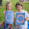 Hannah Shabrack (left), 3, and Rebecca Shabrack, 8, hold up their rendition of the solar eclipse outside of Taylor Library in North Mankato. Photo by Jackson Forderer