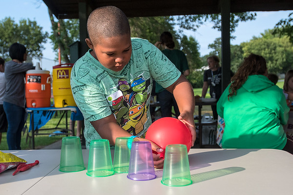Charlie Johnson, 9, uses air from a balloon to blow cups off of a table at a mini-game at the YMCA's 50th anniversary celebration of its brother/sister program on Thursday at Tourtellotte Park. Photo by Jackson Forderer