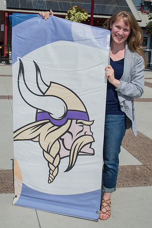 Anna Thill holds a Vikings banner that was formerly hung on street lamp poles around Mankato during Vikings training camp. Photo by Jackson Forderer