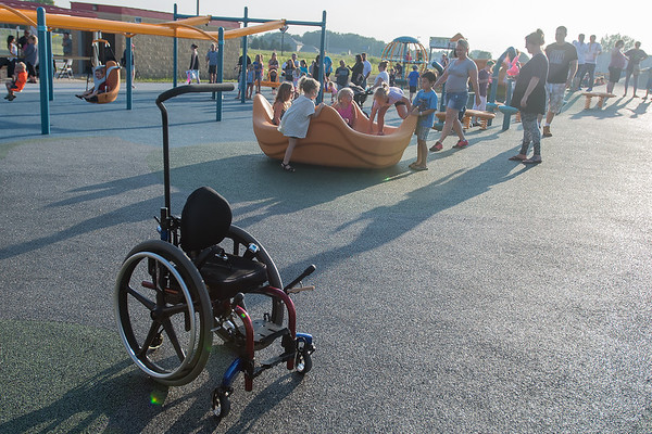 """Henry Ireland's wheelchair sits vacant as he and others play on the newly opened Fallenstein Playground. When asked what his favorite part of the park was, Henry, 3, who has spina bifida, replied, """"All of it."""" Photo by Jackson Forderer"""