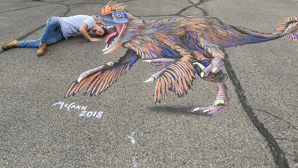 Vusa Bentley of Mankato does as many did throughout the day, and poses with a piece of 3D chalk artwork made by Shawn McCann from Minneapolis at the first annual 3D Chalk Festival. McCann said that he had difficulties finishing the piece, as people wanted to pose with it before he was done. Photo by Jackson Forderer